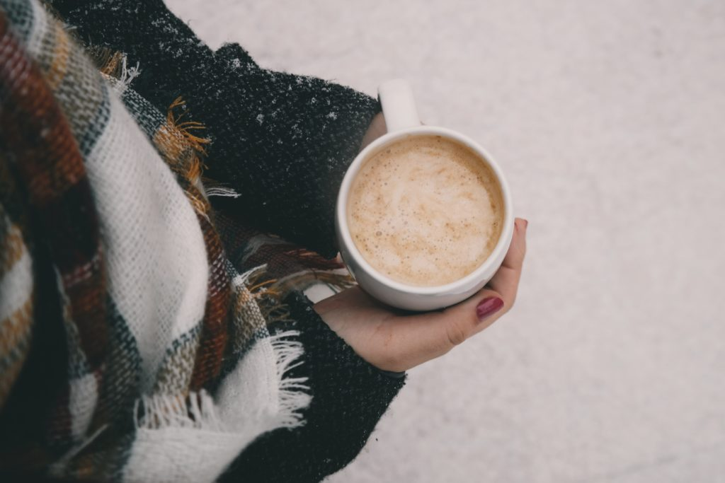 Woman outside in the snow with a hot beverage